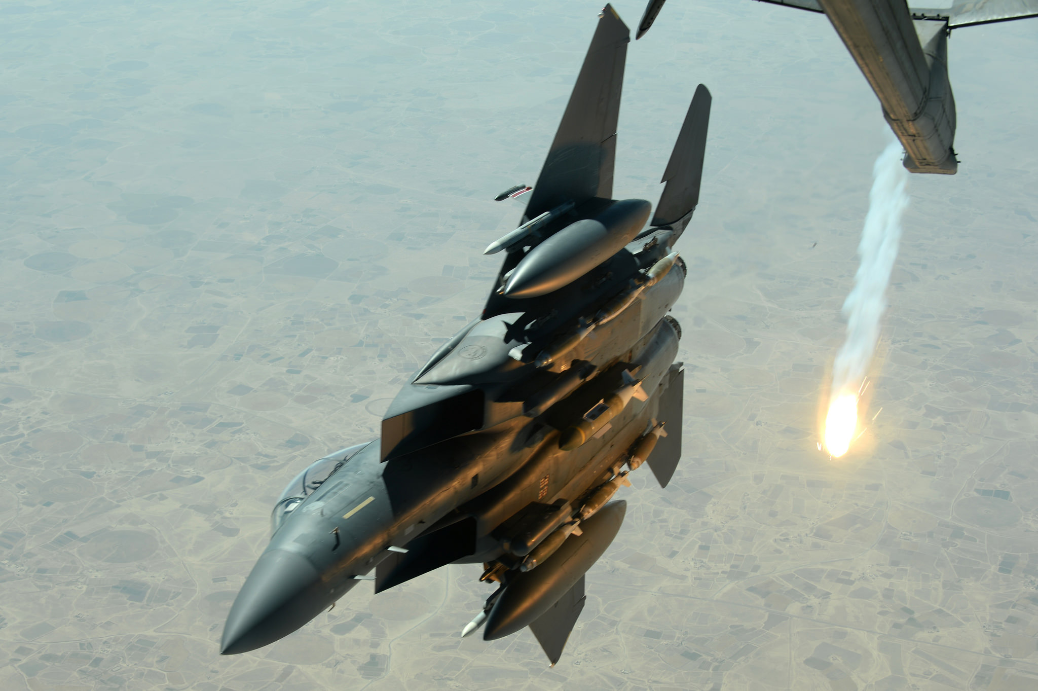 A U.S. Air Force F-15E Strike Eagle pops a flare while departing after refueling with a USAF KC-10 Extender aircraft over Southwest Asia in support of Operation Inherent Resolve, Aug. 30, 2015. U.S. Air Force photo by Staff Sgt. Sandra Welch