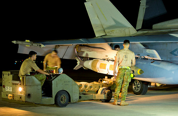 Air Task Group Strike Element Armament Technicians load ordnance on to an F/A-18A Hornet on the flight line of Australia's main air operating base in the Middle East region. [Aus DoD]
