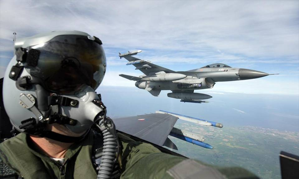 A pilot sits in the cockpit of a Dutch F16 with a second F-16 in the sky in the background (Dutch MoD)
