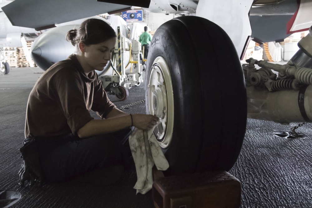 An Aviation Structural Mechanic assigned to the Fighting Swordsmen of Strike Fighter Squadron (VFA) 32 cleans the landing gear of a F/A-18E Super Hornet in the hangar bay of the aircraft carrier USS Dwight D. Eisenhower (US Navy)