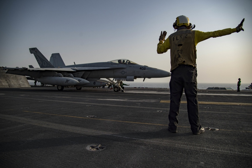 Aviation Boatswain's Mate 1st Class Jeremy Parrish, a native of Apopka, Fla., directs an F/A-18E Super Hornet assigned to the Gunslingers of Strike Fighter Squadron (VFA) 105 on the flight deck of the aircraft carrier USS Dwight D. Eisenhower (CVN 69) (Ike) (via US Navy)