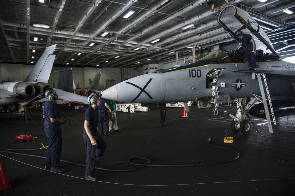 ailors cunduct low power turn test of an F/A-18F Super /hornet assigned to the Fighting Swordmen of Strike Fiighter Squadron of (VFA) 32 in the hangar bay of the aircraft carrier USS Dwight D. Eisenhower (US Navy)