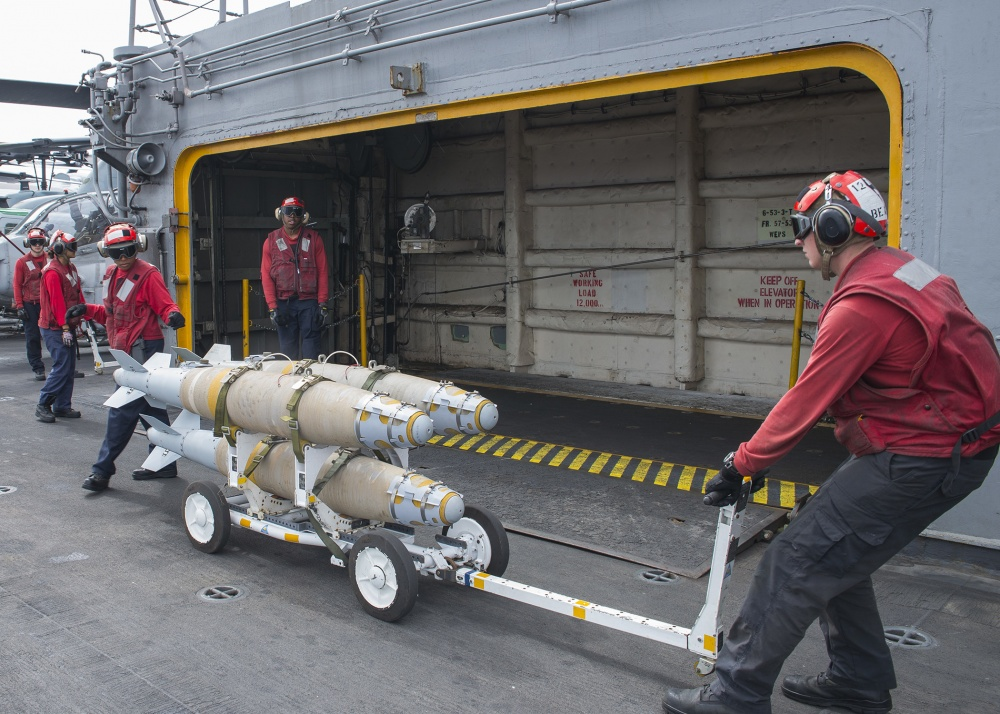 Sailors move GBU-54 laser joint direct attack munition bombs onto an elevator aboard USS Wasp, Oct 6th (US Navy)