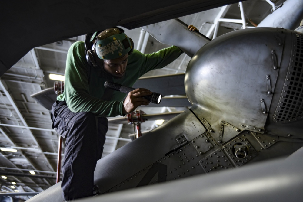 A corrosion inspection is carried out on a MH-60S Sea Hawk helicopter assigned to the Dusty Dogs of Helicopter Sea Combat Squadron (HSC) 7 in the hangar bay of the aircraft carrier USS Dwight D. Eisenhower, Oct 11th (US Navy)