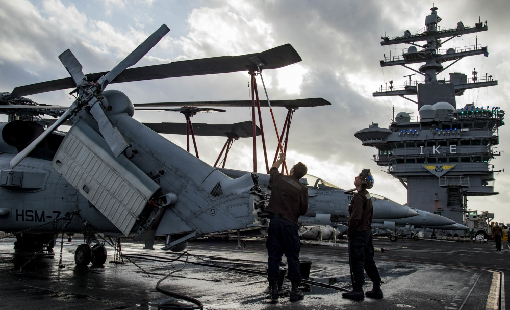 An MH-60R Sea Hawk helicopter is washed down on USS Dwight D. Eisenhower, Dec 2nd (US Navy)